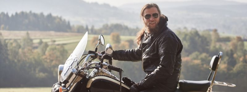 bearded motorcyclist man with long hair in black leather jacket