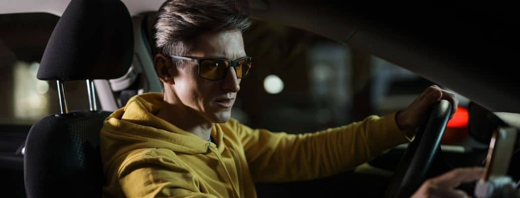 man at night with driving glasses car dashboard