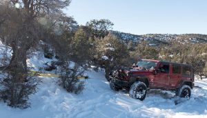red jeep using winch in a snow