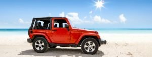 red jeep with soft top at beach